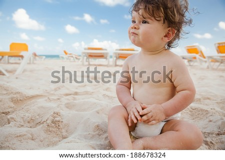 Little boy with curly hair on the sunny beach of Mexico. - stock photo