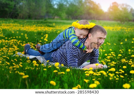 little boy with dad walking on a flowering spring meadow. - stock photo