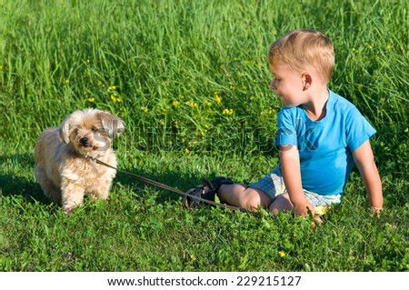 Little boy with dog in grass