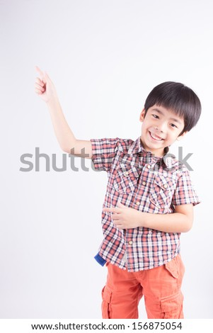 Little boy with empty pointing lifted up hand - stock photo