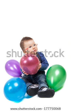 Little boy with eyeglasses playing with colorful balloons - stock photo