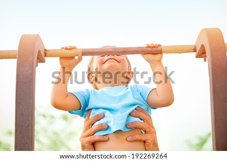 Little boy with fathers help catch up on the horizontal  bar, active childhood, cute small acrobat, workout on backyard, summer camp concept - stock photo