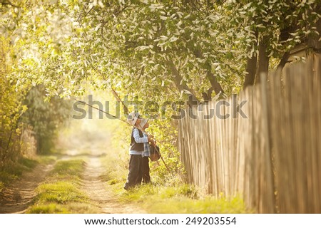 Little boy with fishing rods go on a fishing trip on the narrow rural road in sunny summer day - stock photo