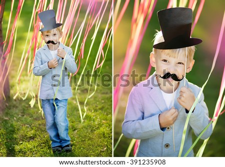 little boy with funny paper mustache and hat. Cheerful children's holiday outdoors. - stock photo