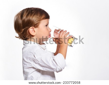 Little boy with glass of juice on white background.
