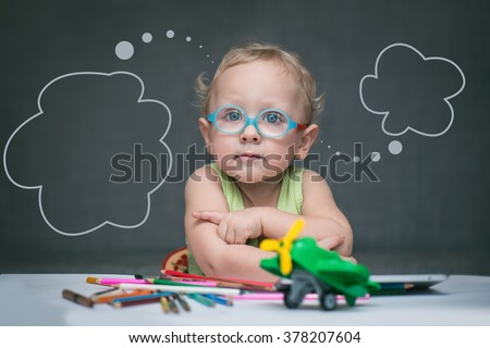 Little boy with glasses sits at a table on which are scattered crayons and toys - stock photo