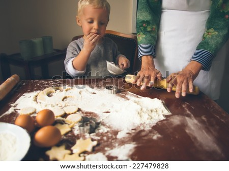 Little boy with grandmother preparing and eating Christmas cookies. - stock photo