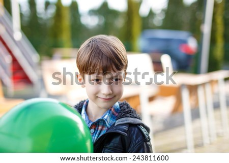 Little boy with green balloon, outdoor portrait - stock photo