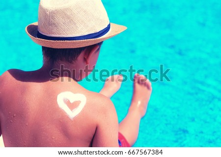 Little boy with hat next to the swimming pool