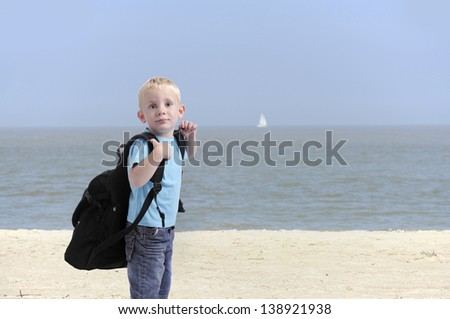 little boy with heavy backpack , outdoors at the beach - stock photo