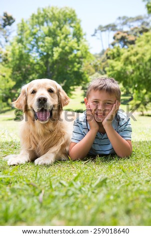 Little boy with his dog in the park on a sunny day - stock photo