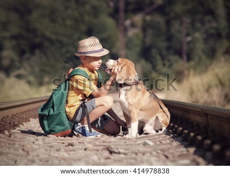 Little boy with his dog sitting on the railway - stock photo