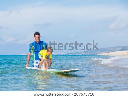 Little boy with his father learning surfing - stock photo