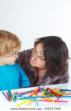 Little boy with his mother draws with color pencils on a white background - stock photo