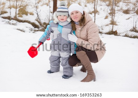 little boy with his mother walks in the snow