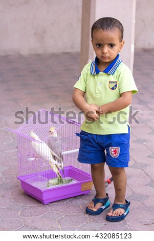 Little boy with his pet birds. Nizwa, Oman - 27/MAY/2016