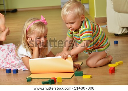 little boy with his sister playing at home