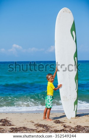 Little boy with his surfboard on the beach - stock photo