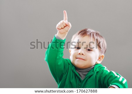 Little boy with idea showing finger upward over grey backgound - stock photo