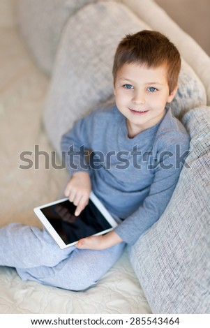 Little boy with iPad sitting on the sofa - stock photo