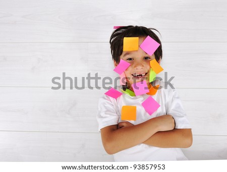 Little boy with memo posts on his face - stock photo
