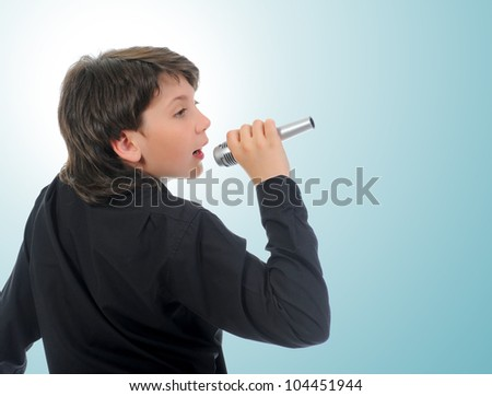 Little boy with microphone sings a song.  on a blue background - stock photo