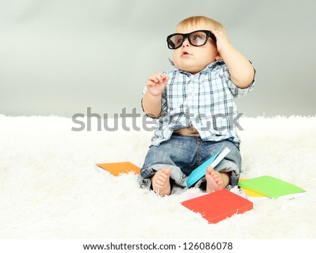 Little boy with multicolor books, on white carpet - stock photo