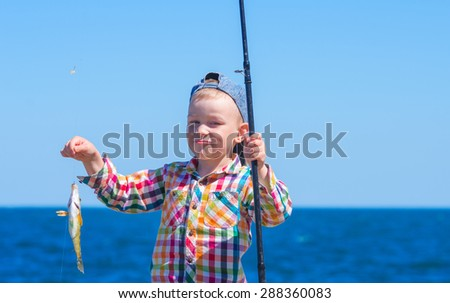 "Little boy with mysterious sight holding a fishing pole with his first catch - ""Symphodus tinca"". Family composition"