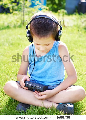 Little boy with old audio cassette player and headphones - stock photo