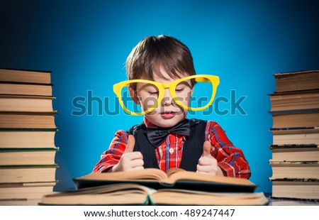 little boy with open books and funky glasses