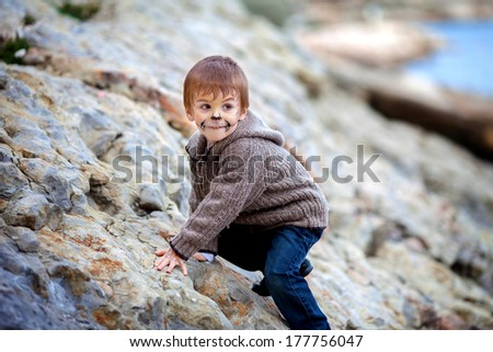 Little boy with painted face on the beach
