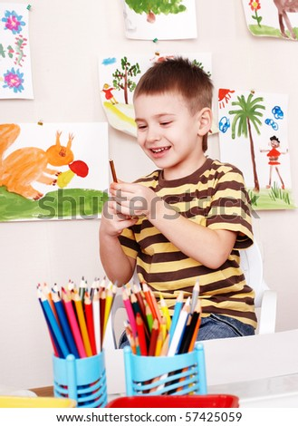 Little boy with pencil in play room. - stock photo