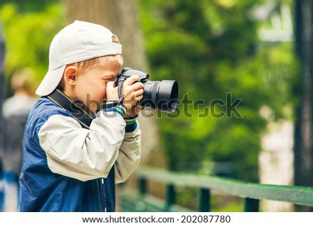 Little boy with photo camera makes a shoot - stock photo