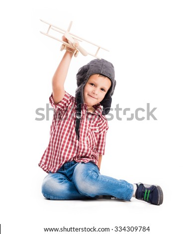 little boy with pilot hat and toy airplane sitting isolated on white background - stock photo