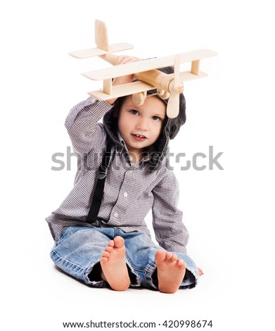 little boy with pilot hat playing toy plane isolated on white background - stock photo