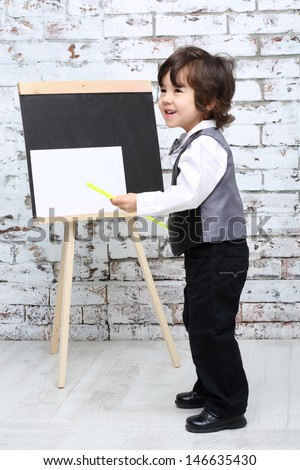 Little boy with pointer stands next to chalk board with sheet in studio. - stock photo