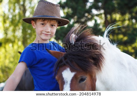 Little boy with pony on farm, horse therapy - stock photo