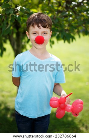 Little boy with red clown nose and balloon dog - stock photo