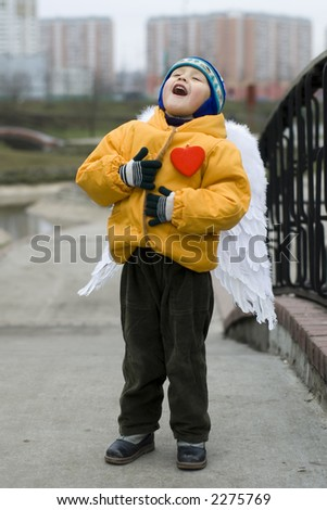 little boy with red heart as angel outdoors - stock photo
