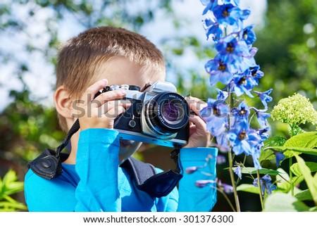 Little boy with retro SLR camera shooting macro of blue flowers - stock photo