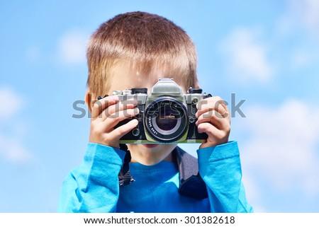 Little boy with retro SLR camera shooting on blue sky - stock photo
