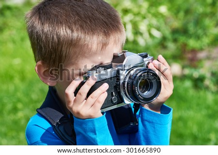 Little boy with retro SLR camera shooting outdoors - stock photo