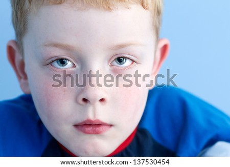 little boy with sad expression and watery eyes - stock photo
