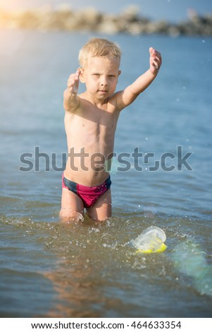 Little boy with snorkel by the sea. Cute little kid wearing mask and flippers for diving at sand tropical beach. Ocean coast.