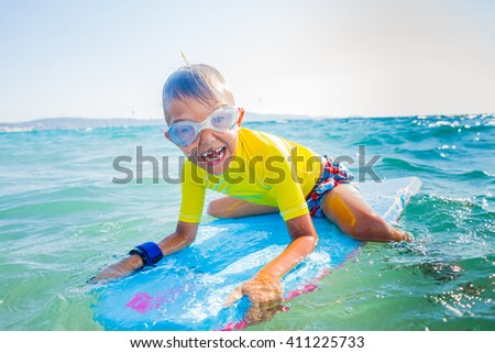 Little boy with surf board having fun in sea against sea