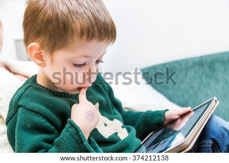 little boy with tablet pc computer at home