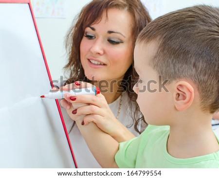 Little boy with teacher near whiteboard - stock photo