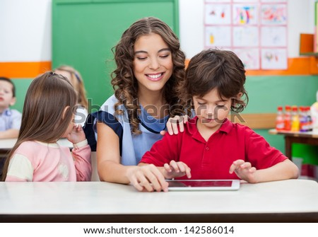 Little boy with teacher using digital tablet in kindergarten - stock photo