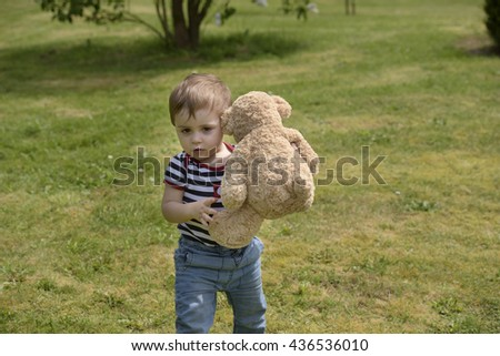 little boy with teddy bear outdoors - stock photo