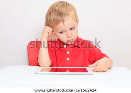 little boy with touch pad, early learning - stock photo